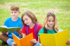 儿童在公园的阅读书Droup  免版税图库摄影