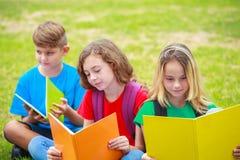 儿童在公园的阅读书Droup  免版税库存照片