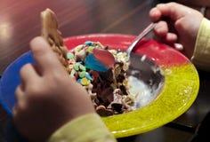 儿童在冰吃的` s手一个五颜六色的冰淇凌盘 图库摄影
