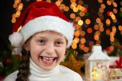 儿童在圣诞老人帽子有圣诞节装饰的,黑暗的背景与光,面孔表示和愉快的情感, winte的女孩画象 免版税库存图片