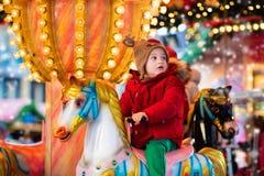 儿童在圣诞节市场上的骑马转盘 图库摄影