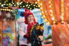 儿童在圣诞节市场上的骑马转盘 免版税库存图片