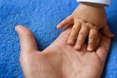 儿童在妇女的棕榈的` s手 免版税库存照片