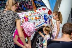 儿童在汽车的油漆水彩在车展期间 库存图片