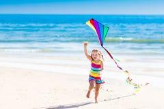 儿童在热带海滩的飞行风筝 免版税库存照片