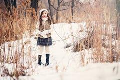 儿童在舒适温暖的室外冬天步行的女孩画象 库存图片