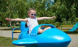 儿童在蓝色飞机吸引力在城市公园,愉快的童年,暑假概念的女孩飞行 免版税库存照片