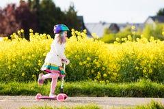 儿童在途中的骑马schooter对学校 库存图片
