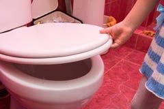 儿童在洗手间盒盖和位子下的` s手 免版税库存照片