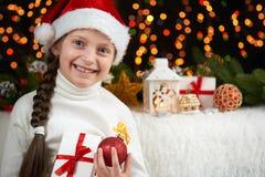 儿童在黑暗的背景与圣诞节装饰,面孔表示和愉快的情感的女孩画象,在圣诞老人帽子,冬天穿戴了 免版税库存照片