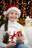 儿童在黑暗的背景与圣诞节装饰,面孔表示和愉快的情感的女孩画象,在圣诞老人帽子,冬天穿戴了 库存图片