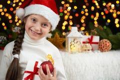 儿童在黑暗的背景与圣诞节装饰,面孔表示和愉快的情感的女孩画象,在圣诞老人帽子,冬天穿戴了 库存照片