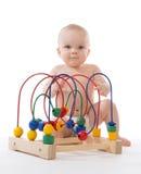 儿童坐和演奏木教育玩具的小小孩 免版税库存照片