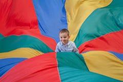 儿童坐在操场彩虹降伞的中心的男孩小孩 免版税图库摄影
