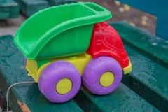 儿童塑料玩具卡车在长凳的公园 库存照片