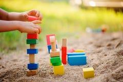 儿童大厦五颜六色的木砖玩具房子在沙盒的 库存图片