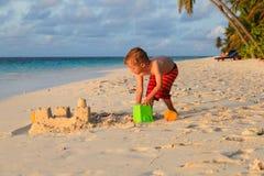 儿童大厦在日落海滩的沙子城堡 免版税库存照片