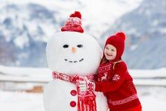 儿童大厦雪人 孩子修造雪人 使用户外在多雪的冬日的男孩和女孩 在圣诞节的室外家庭乐趣 免版税库存图片