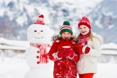 儿童大厦雪人 孩子修造雪人 使用户外在多雪的冬日的男孩和女孩 在圣诞节的室外家庭乐趣 库存图片