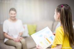 儿童女儿祝贺妈妈并且给她的绘画 拥抱的妈咪和的女孩微笑和 家庭假日和幸福 免版税库存照片