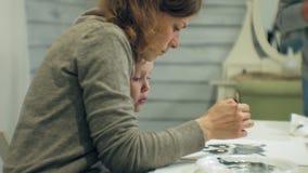 儿童女孩一起坐在与他们的手指和油漆的桌在教室和图画上 他们他们 股票视频