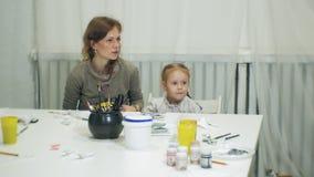 儿童女孩一起坐在与他们的手指和油漆的桌在教室和图画上 他们他们 影视素材