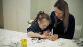 儿童女孩一起坐在与他们的手指和油漆的桌在教室和图画上 他们他们 股票录像