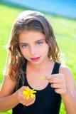 儿童女孩与雏菊花的测试爱 免版税库存图片