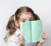儿童女孩举行笔记本空的页 浓缩消息的通信 免版税库存照片