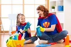 儿童女孩和她的母亲有清洁物品的在家 图库摄影