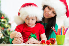 儿童女孩和母亲给圣诞老人的文字信件 库存照片