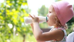 儿童女孩喝从瓶或牛乳气酒的牛奶饮料,微笑并且显示从酸奶的一根白色髭 股票录像