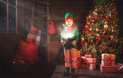 儿童女孩圣诞老人矮子帮手与一件不可思议的圣诞节礼物的 免版税库存照片