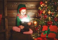 儿童女孩圣诞老人矮子帮手与一件不可思议的圣诞节礼物的 库存照片