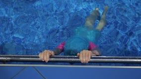 儿童女孩在举行在金属扶手栏杆的游泳场潜水在水面下 股票视频