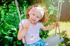 儿童女孩在夏天庭院里嗅到在摇摆的花 免版税图库摄影
