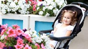儿童女孩在婴儿车坐并且微笑 影视素材