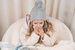 儿童女孩在家椅子的以在手帕的温暖的被编织的帽子羊毛一揽子喷嚏 季节秋天冬天寒冷 免版税图库摄影