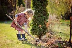 儿童女孩在有铁锹的春天庭院里帮助 免版税库存图片