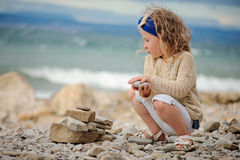 儿童女孩在海滩的建筑石料塔在夏日 库存图片