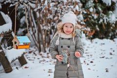 儿童女孩在鸟饲养者投入种子在冬天多雪的庭院里 图库摄影