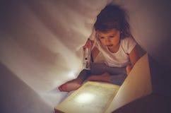 儿童女孩在黑暗的阅读书,在盖子下在床上与光 免版税图库摄影