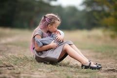 儿童女孩坐与她新出生的兄弟的草在同水准的步行的 免版税库存照片