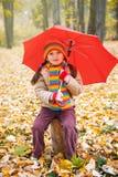 儿童女孩坐与红色伞的树干在秋天森林,在背景,秋季的下落的叶子里 免版税库存照片
