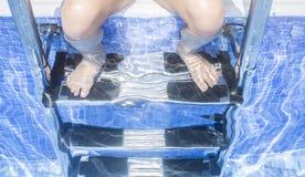 儿童女孩坐与腿underwa的游泳池梯子 库存图片