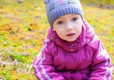 儿童女孩坐的青苔周道的神色 免版税图库摄影