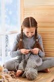 儿童女孩坐窗口基石并且编织从灰色毛纱的围巾 美丽的景色窗口外-好日子 免版税库存照片