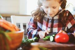 儿童女孩帮助妈妈烹调和切开沙拉的新鲜蔬菜与刀子 图库摄影