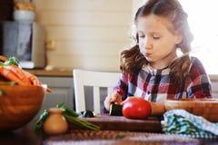 儿童女孩帮助妈妈烹调和切开沙拉的新鲜蔬菜与刀子 免版税库存照片