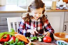 儿童女孩帮助妈妈烹调和切开沙拉的新鲜蔬菜与刀子 库存图片